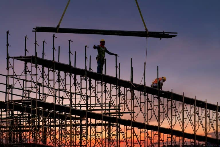 Man working on construction site with scaffold and building with sunset background,scaffolding for construction factory